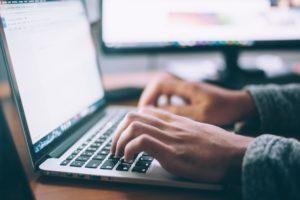 man typing on the laptop